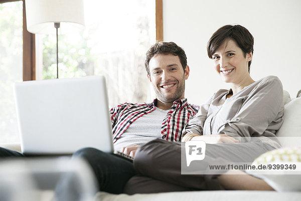Entspannen Sie sich gemeinsam auf dem Sofa mit dem Laptop.