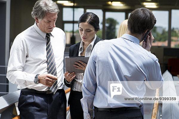 Geschäftsfrau zeigt Kollegin digitales Tablett