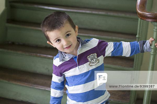 Junge steht unten an der Treppe  lächelnd  Portrait