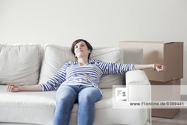 Frau beim Umzug auf dem Sofa liegend