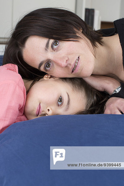 Mutter und Tochter liegen zusammen auf dem Bett  Porträt
