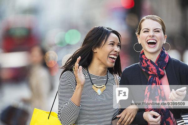 Frauen  die zusammen lachen  gehen die Straße entlang.