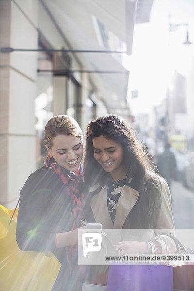 Frauen schauen gemeinsam auf das Handy in der Stadtstraße