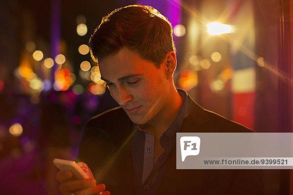Mann mit Handy in der Stadt bei Nacht