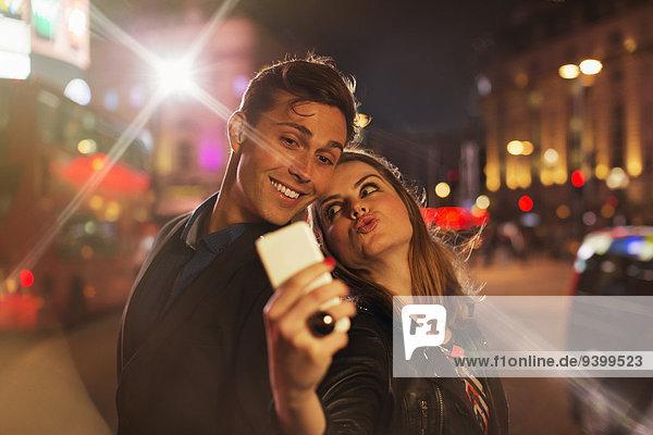 Paar fotografiert zusammen mit dem Handy bei Nacht