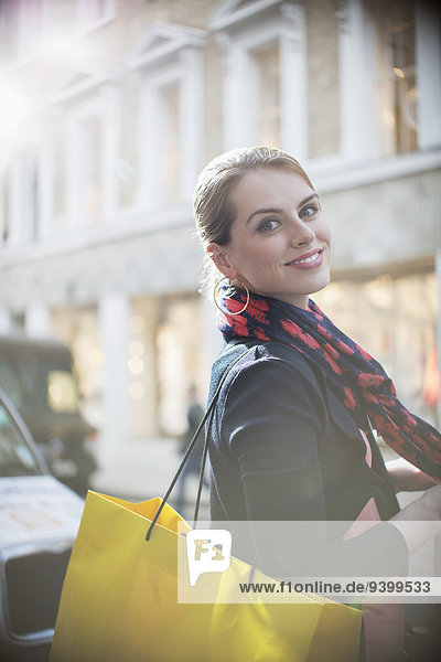 Frau mit Einkaufstasche überquert Stadtstraße