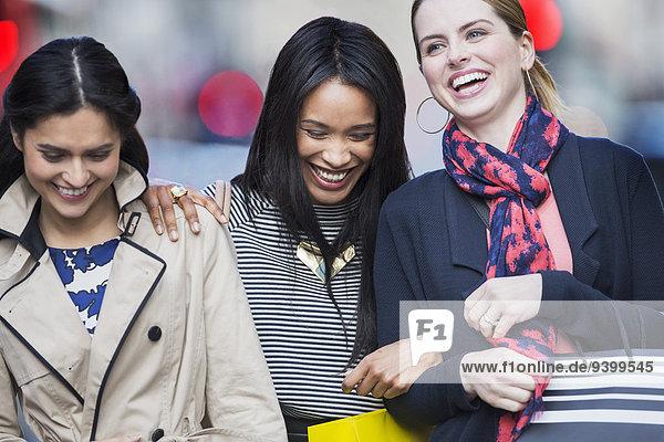 Frauen  die zusammen auf der Straße lachen.