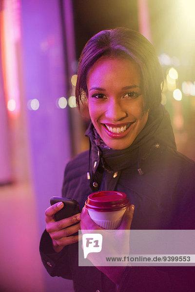 Frau auf der Stadtstraße mit Kaffee und Handy bei Nacht