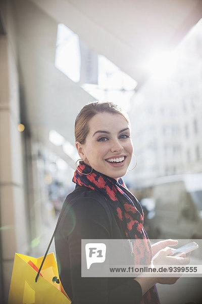 Frau mit Handy in der Stadtstraße