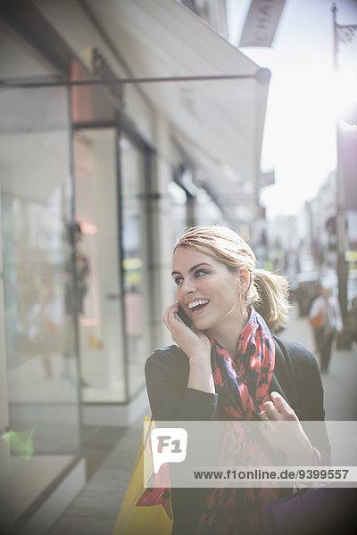 Frau  die auf dem Handy spricht  während sie die Straße entlang geht.