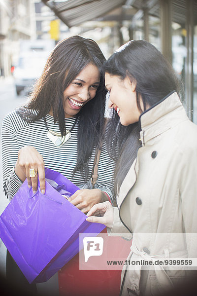 Frauen schauen gemeinsam durch die Einkaufstasche auf der Stadtstraße