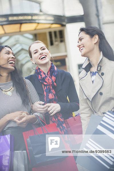 Freunde lachen gemeinsam auf der Stadtstraße