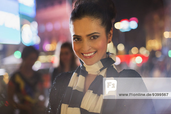 Frau lächelt nachts auf der Stadtstraße