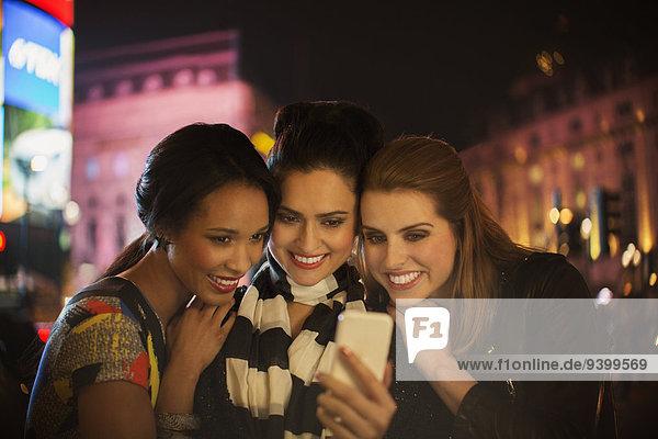 Frauen  die nachts auf der Straße miteinander reden.