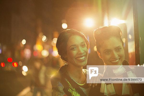 Frauen  die nachts auf der Straße lächeln.