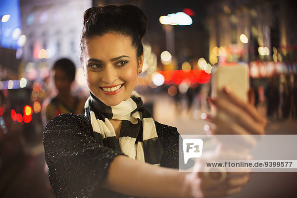 Frau fotografiert nachts mit dem Handy