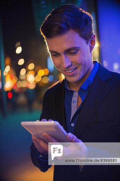 Mann mit digitalem Tablett auf der Stadtstraße bei Nacht