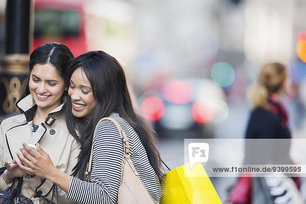 Frauen schauen auf das Handy in der Stadtstraße