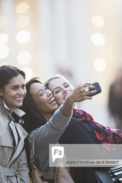 Friends talking picture with cell phone together on city street