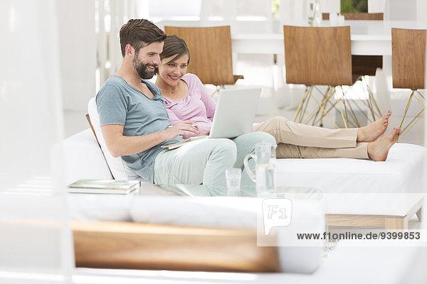 Paar mit Laptop zusammen auf der Liege im modernen Wohnzimmer