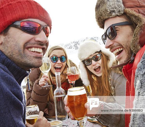 Freunde feiern mit Getränken im Schnee