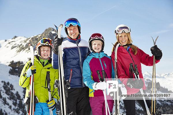 Lächelnde Familie mit Skistöcken am Berg