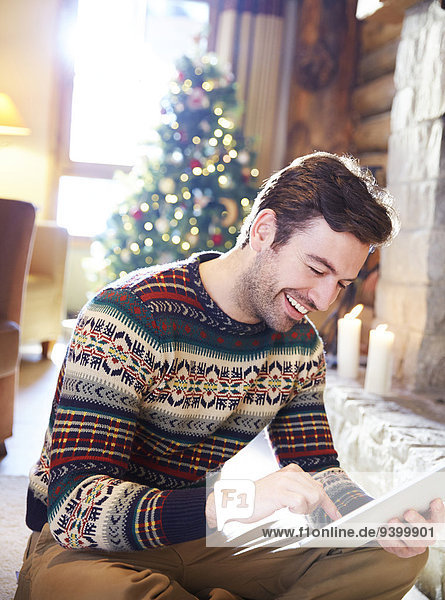 Mann mit digitalem Tablett im Blockhaus