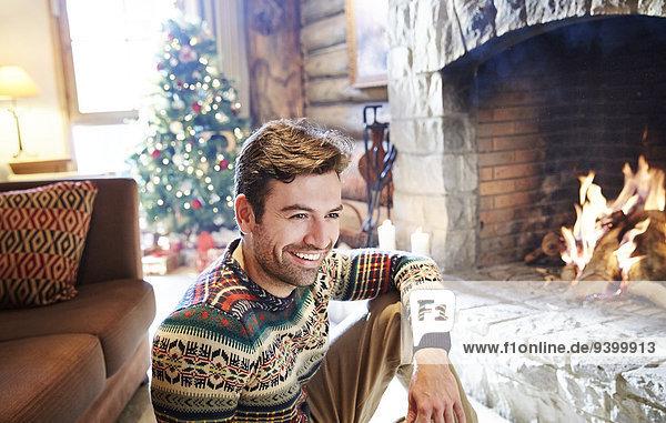 Mann im warmen Pullover genießt den Kamin