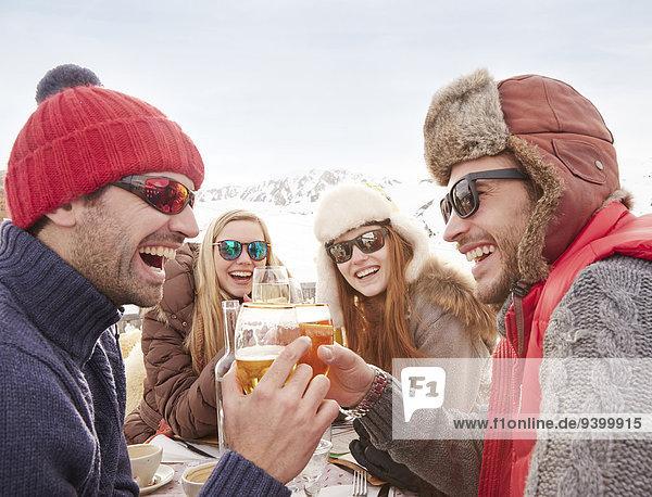 Freunde beim Feiern mit Getränken im Schnee