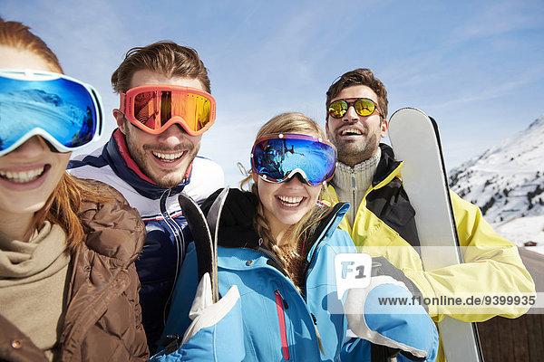 Freunde mit Skiern auf dem Berggipfel