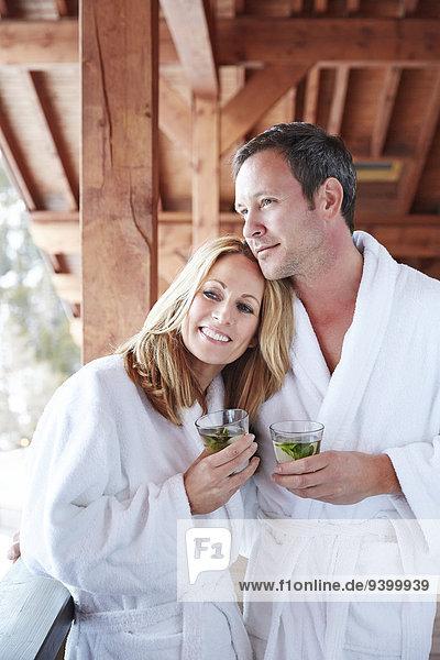 Paar in Bademänteln  die sich auf dem Balkon umarmen