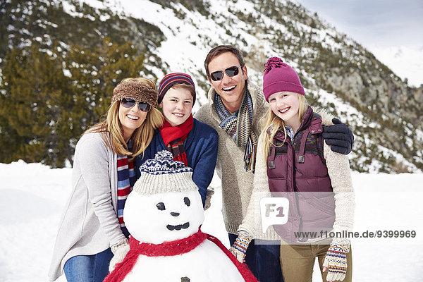 Familie baut gemeinsam einen Schneemann