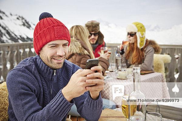 Mann mit Handy auf dem verschneiten Balkon
