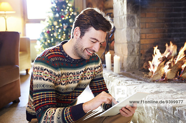 Man using digital tablet in front of fireplace