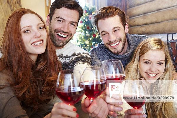 Freunde stoßen sich gegenseitig mit Wein an.