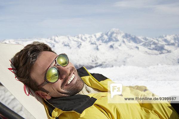 Mann auf einem Stuhl im Schnee liegend