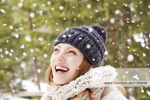 Frau  die den Schnee bewundert  der draußen fällt.