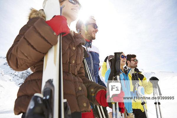 Freunde stehen mit Skiern auf dem Berggipfel