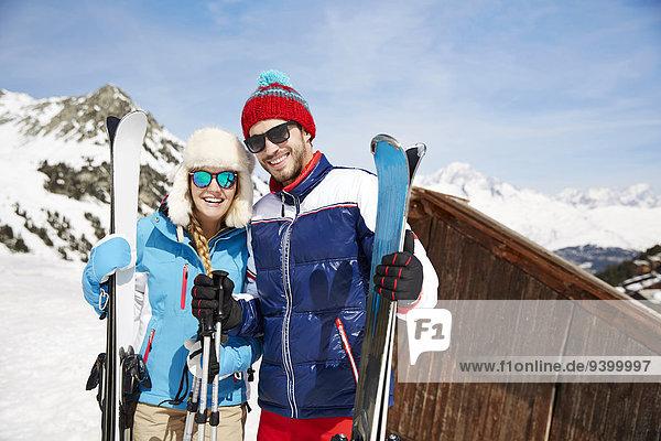 Paar hält Skier am Berg zusammen