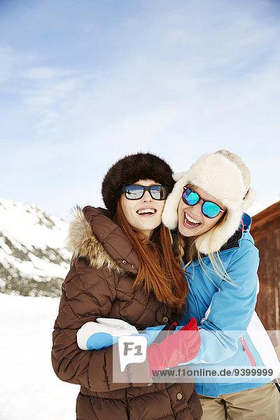 Freunde umarmen sich im Schnee