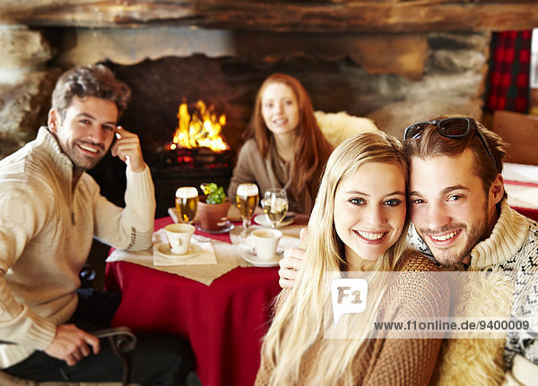 Freunde beim gemeinsamen Essen am Kamin