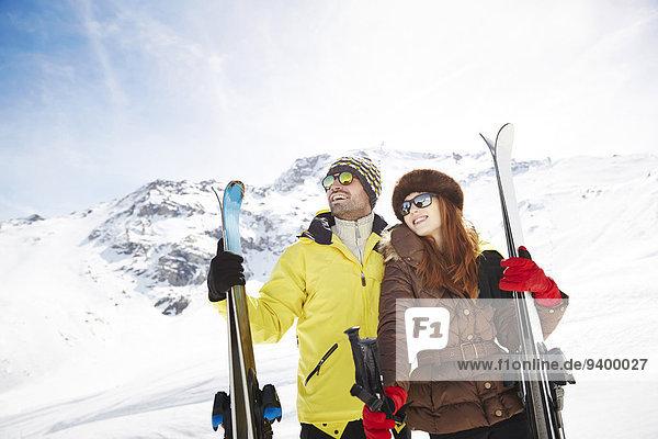 Paar haltende Skier auf dem Berggipfel zusammen