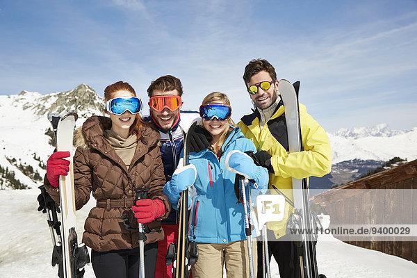 Freunde auf dem Berg halten Skier zusammen.