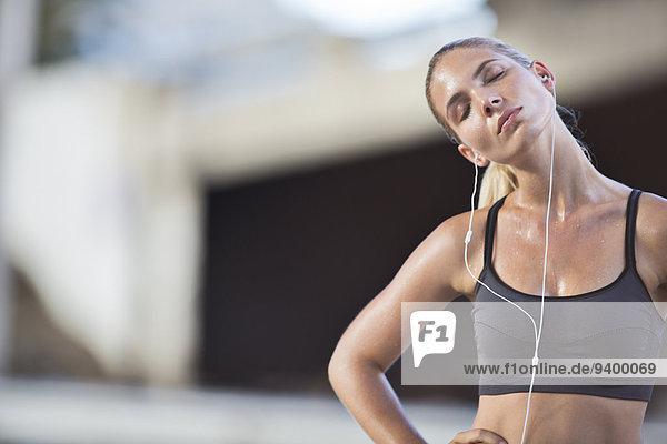 Frau beim Dehnen mit geschlossenen Augen nach dem Training
