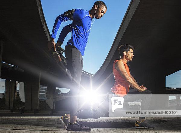 Männer  die sich vor dem Training auf der Straße ausstrecken.