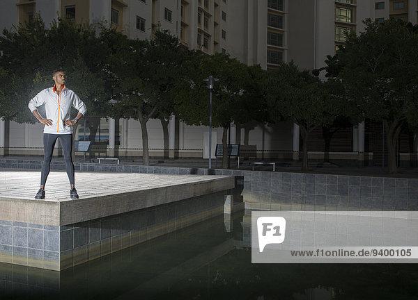 Mann steht nachts im Stadtpark