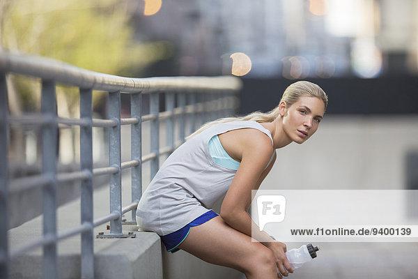 Frau ruht sich nach dem Training auf der Stadtstraße aus.
