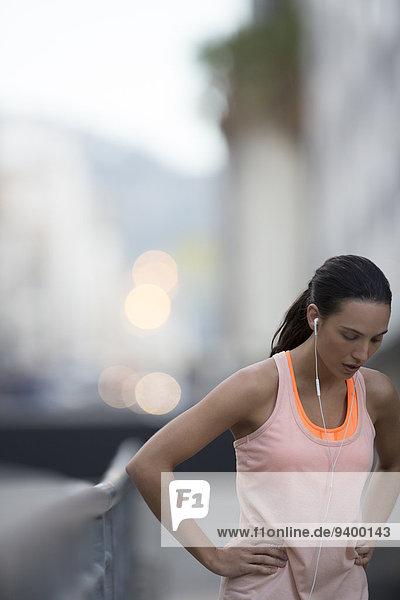 Frau ruht sich nach dem Laufen auf der Stadtstraße aus.