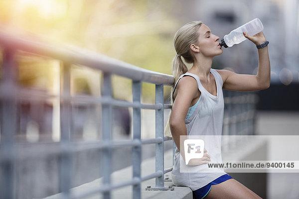 Frau trinkt Wasser nach dem Training auf der Stadtstraße