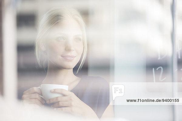 Frau trinkt Kaffee drinnen